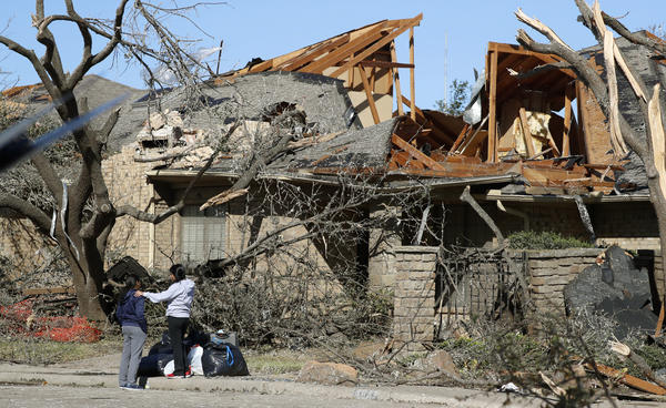 Women stand outside a house damaged by a tornado Sunday night in the Preston Hollow section of Dallas. The city was still cleaning up on Monday.