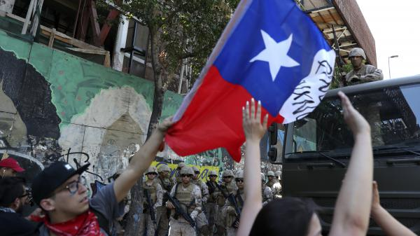 Protesters wave a Chilean national flag in front of military personnel in Santiago on Monday.
