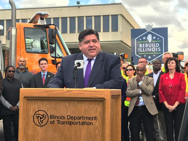 Flanked by state lawmakers and IDOT officials and workers, Gov. J.B. Pritzker announces details of statewide road and bridge construction at IDOT Headquarters in Springfield on Oct. 21