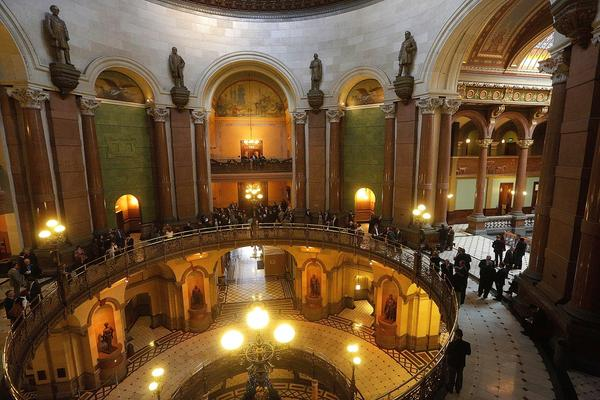 """Lawmakers, lobbyist and visitors stand along the """"Brass Rail"""" outside the House chambers during veto session at the State Capitol in 2016 in Springfield."""
