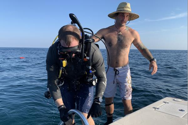 Shawn Campbell helps Justin Herris get back on the boat after a dive at the Circle of Heroes military memorial off the coast of Clearwater, Fla.