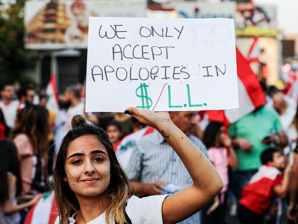 A Lebanese woman holds up a sign demanding that the country's ruling elites pay up on the sixth day of protests in Zouk Mosbeh, north of Beirut, on Tuesday.