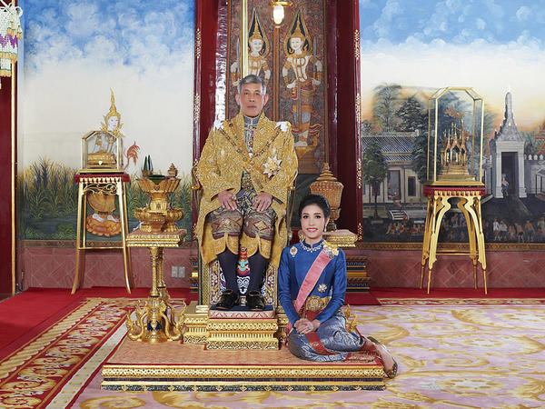 In this undated photo posted Aug. 26, 2019, on the Thailand Royal Office website, Thailand's King Maha Vajiralongkorn sits on the throne with his official consort Sineenatra Wongvajirabhakdi at the royal palace.