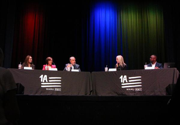 1A Host Joshua Johnson speaking with a panel in Wichita, Kansas.