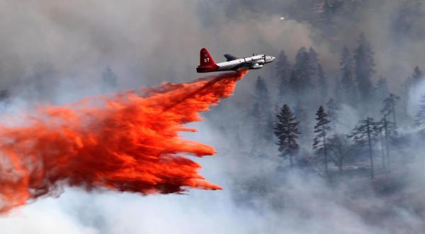 Neptune Aviation air tanker drops retardant on a fire.