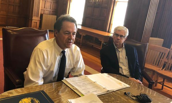 Montana Gov. Steve Bullock and Lt. Gov. Mike Cooney talk with reporters in the State Capitol about state budget cuts, July 25, 2018.