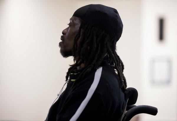 Kwame Dew, a single father of three, sits in his electric wheelchair during a meeting of the Urban Re-Entry Group.