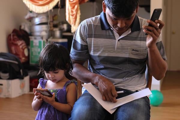A refugee from Burma works to pay his gas bill at his home in Greeley.