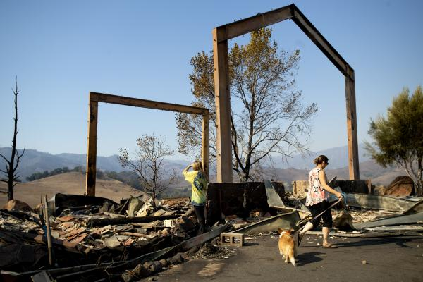 Ashley LaFranchi (left) and Stephanie LaFranchi examine the remains of their family's Oak Ridge Angus ranch, leveled by a wildfire called Kincade Fire, in Calistoga, Calif., on Monday.