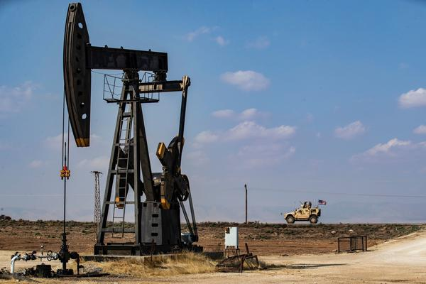 A U.S. military vehicle drives past an oil pump jack in the countryside of Syria's northeastern city of Qamishli. President Trump is leaving some U.S. troops in Syria, with the goal of controlling Syria's oil fields. But legal experts say exploiting the oil could amount to pillaging — a war crime.