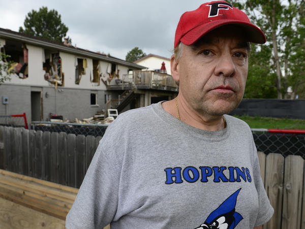 Leo Lech stands on a pile of wood in his neighbor's yard, which overlooks the back of his former home in Greenwood Village, Colo. In 2015, the home was destroyed by the police during a standoff with a gunman and has since been razed and rebuilt. On Tuesday, a federal appeals court ruled that the city does not owe Lech any compensation.