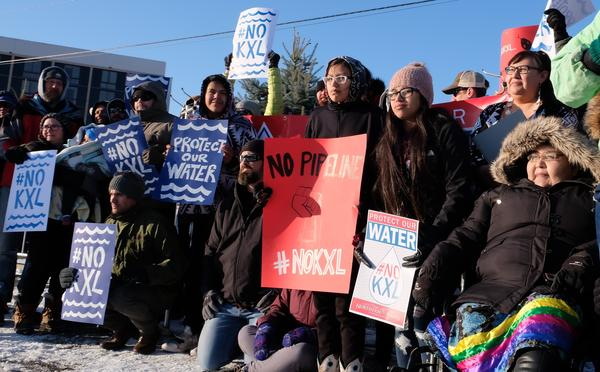 Keystone XL protesters pose for a photo in 19-degree weather ahead of a public meeting in Billings, Mont., on Tuesday. The State Department is collecting public comments on its revised environmental impact statement for the pipeline.