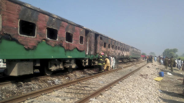 Pakistani officials examine a train damaged by a fire in Liaquatpur, Pakistan, on Thursday. A massive fire engulfed three carriages of the train traveling in the country's eastern Punjab province.