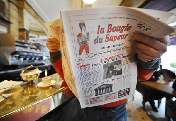 """A man reads a copy of the satirical newspaper <em>La Bougie du Sapeur</em> (The Sapper's Candle), published every leap day, in a Parisian cafe on Feb. 29, 2008. The paper's tagline is """"without reproach."""""""
