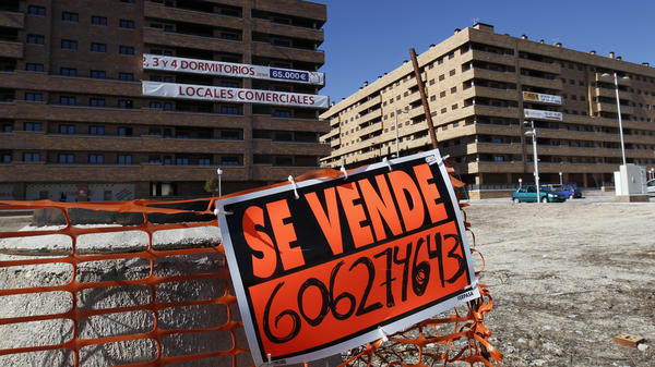 """A """"For Sale"""" sign hangs outside mostly empty apartment blocks in the Madrid satellite town of Sesena in February. Banks are trying to sell billions of euros worth of property left by bankrupt developers. This is attracting bargain-hunting investors from abroad."""