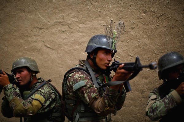 """Afghan commandos line up outside the walls of a mock compound before storming in to clear the area. """"My mission is to advise and teach my non-commissioned officers and make sure they're getting enough equipment, they're getting enough training,"""" Wafa says."""