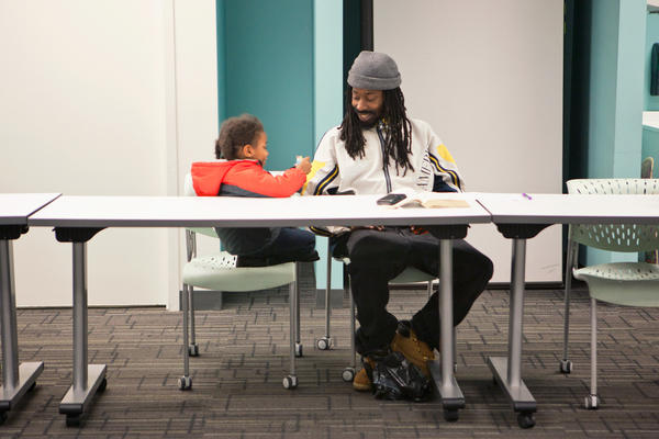 Michael Cornish, right, and his son Naeem, wait for a Responsible Fatherhood meeting to begin at the Center for Urban Families on Nov. 11. The weekly meetings are part of a program for parents to reduce their child support debt.