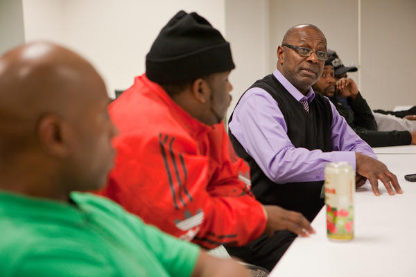 Group leader Eddie White speaks during the meeting. Around two dozen men — 20-something to middle age, in sweats and in suits — sit in a large square each week and discuss topics ranging from parenting, debt and unemployment.