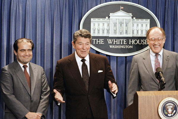 In this June 17, 1986, file photo, President Ronald Reagan speaks at a news briefing at the White House in Washington, where he announced the nomination of Antonin Scalia (left) to the Supreme Court.