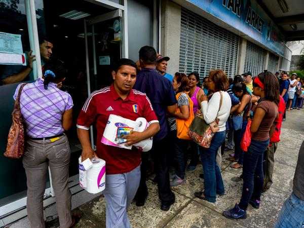 People line up to buy goods at a supermarket in Caracas, Venezuela, on June 13.
