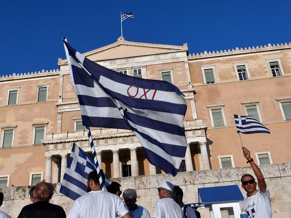 "Protesters hold Greek flags, including one saying ""No,"" during a demonstration at the Greek parliament on July 5, marking the first anniversary of a referendum in which Greeks voted against austerity. Soon after the vote, the prime minister accepted a new bailout deal for Greece imposing even tougher austerity than before."