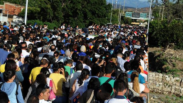 Venezuelans wait in San Antonio del Tachira, Venezuela, to cross the border with Colombia during a rare 12-hour opening Sunday. Thousands of Venezuelans crossed to buy food and medicine.