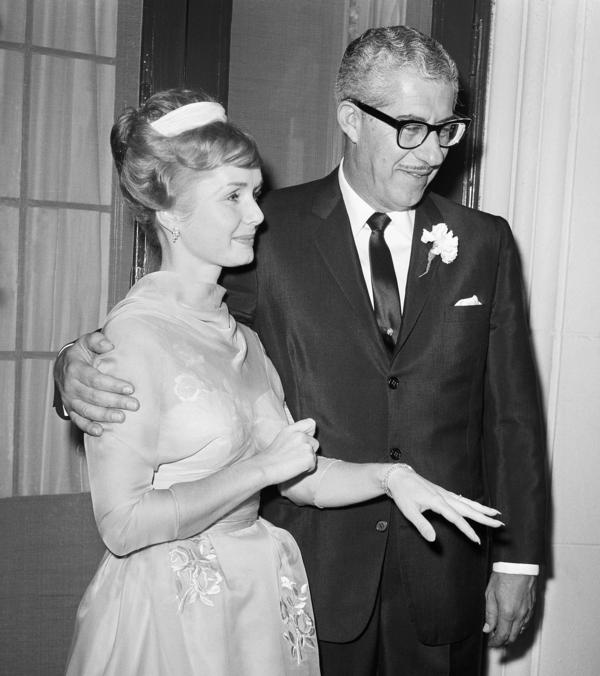 Debbie Reynolds holds out her hand to display her wedding ring as she stands beside multimillionaire shoe magnate Harry Karl following their wedding at Beverly Hills, Calif., in 1960.