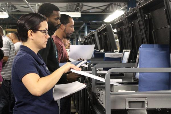 Hillsborough County Supervisor of Elections staff feed hundreds of mock ballots into voting maching to test their accuracy ahead of the primary.