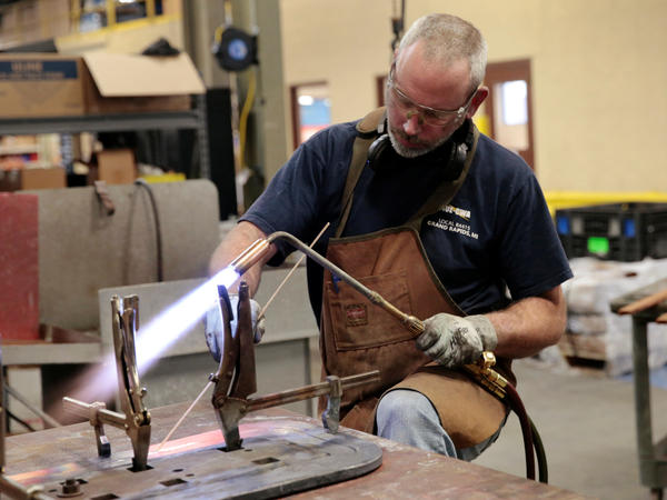 Nate Poort works on braizing loops together for transformers at RoMan Manufacturing in Grand Rapids, Mich., on Dec. 12, 2018.
