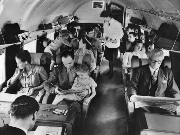 Airplane passengers fly on a British plane in 1960. Travelers can often exhibit bizarre behaviors as a result of the conditions within the airplane cabin.