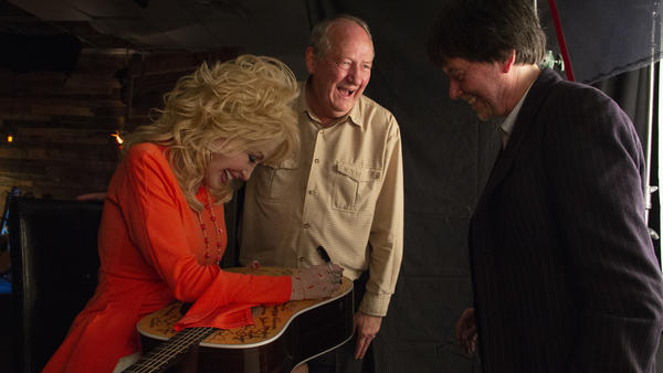 Country star Dolly Parton, signing a guitar alongside writer Dayton Duncan (center) and filmmaker Ken Burns (right).