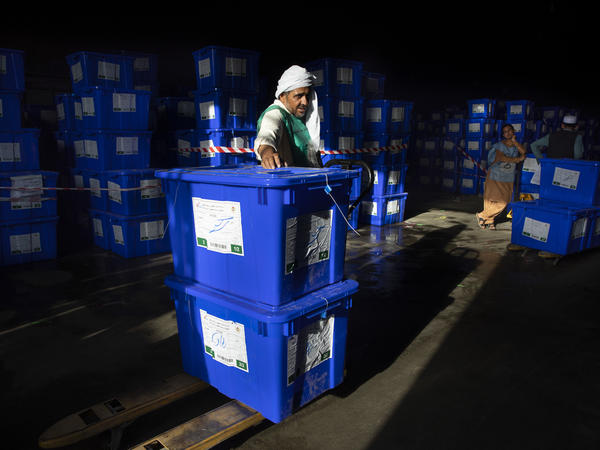 Afghan workers move ballot boxes to trucks getting ready for Saturday's presidential elections in Kabul, Afghanistan. The lead-up to the vote has been marred by violence and uncertainty.