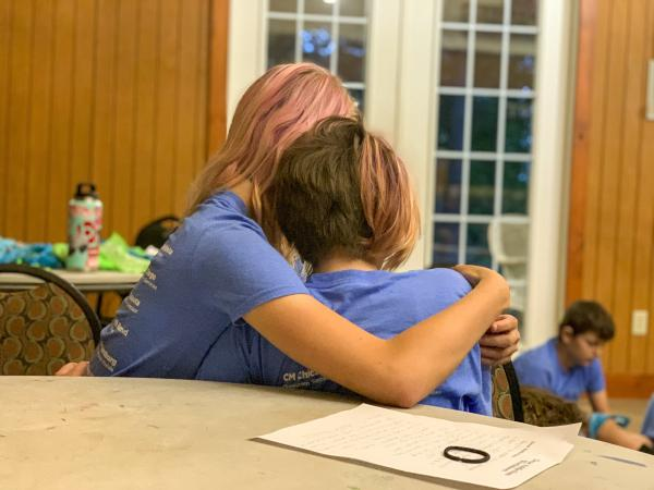Two 12-year-olds comfort each other while sharing stories about their families. Some say it's only at camp that they don't feel alone because they meet other children in their situation. Some children have seen their parents overdose and some have had to call 911. Many have been taken away to foster care multiple times.