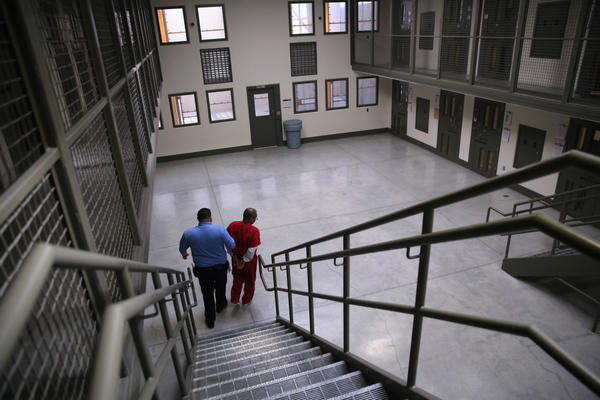 A guard escorts an immigrant detainee from his 'segregation cell' back into the general population at the Adelanto Detention Facility, a private detention center operated by Florida-based GEO Group.  (John Moore/Getty Images)