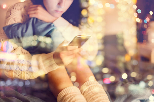 Girl texting on smartphone at home