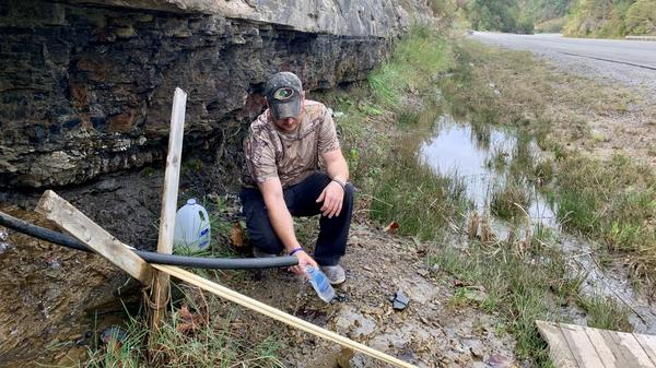 Jasper Davis gets drinking water from a mountain stream in Martin County, Ky. He says he's one of many in the struggling coal region who have trouble affording their water bill.