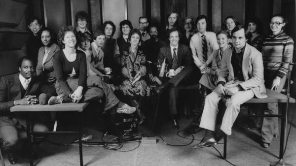A staff photo taken during the early days of <em>Morning Edition. </em>Co-host Bob Edwards is in the back row, standing seventh from the left among the three men in glasses. His co-host, Barbara Hoctor, sits on the table at right, holding a mug. Hoctor left the show after a few weeks. Edwards was host until 2004, when he went to SiriusXM.