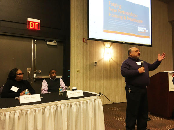 Carlos DeJesús Rivera with the Center for Housing and Health speaks during a housing conference in Bloomington with Patricia Stokes and Armando Smith from Housing Forward.