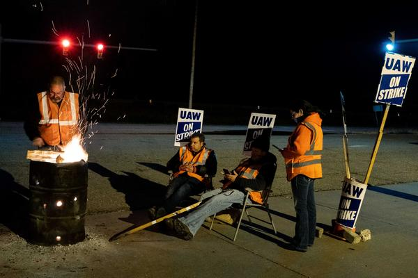 From left: Dan Santangelo, Jeff Sandquist jr, Jeff Kovach and Agnes Hernandez, all former workers at the GM Lordstwon Assembly Plant, gather around a burn barrel in front of the plant on strike.