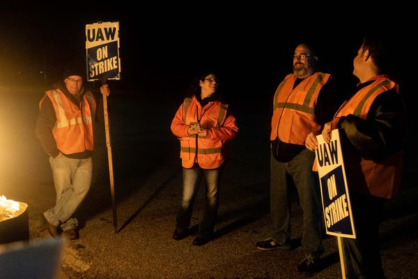 From left, Dan Santangelo, John Sandquist Jr., Jeff Kovach and Agnes Hernandez gather around a burn barrel on the picket line in front of the GM Lordstown Assembly Plant.