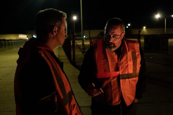 Dan Santangelo (right) reads highlights of the then proposed, now ratified, UAW-GM contract to John Sandquist jr, Santangelo's friend and fellow worker of 25 years, while holding the picket line in front of the now shuttered GM Lordstwon Assembly Plant.