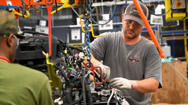 Workers assemble engines along the line at a General Motors plant in Spring Hill, Tenn. A nationwide strike by the United Automobile Workers at GM plants didn't hurt U.S. job growth in October.