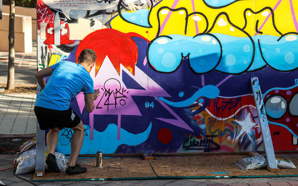Kaelan Dean, a student at New College, spray paints a replica of the Berlin Wall, September 2019. Thomas Iacobucci/WUSF