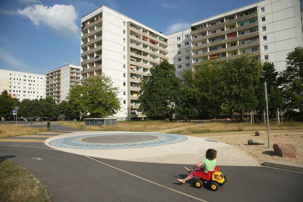 A child plays near communist-era apartment blocks in Hoyerswerda, Germany. After the collapse of the communist East German government that had redeveloped the area into an industrial hub, factories shut down and coal production declined. The population has sunk below 33,000 — about half its size before the fall of the Berlin Wall.