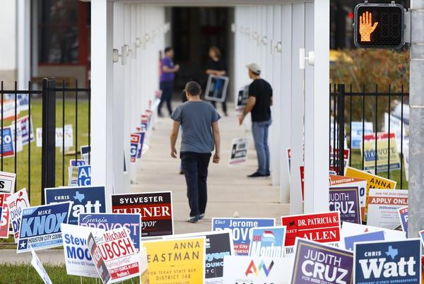 Campaign workers make pitches to voters outside the Metropolitan Multi-Service Center in Houston on Tuesday.
