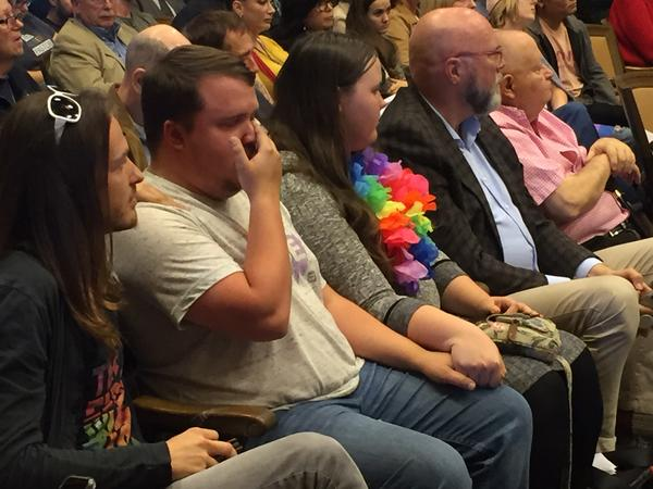 Zachary Mallory (in gray) is comforted after testifying about his experience. He calls himself a survivor of conversion therapy.