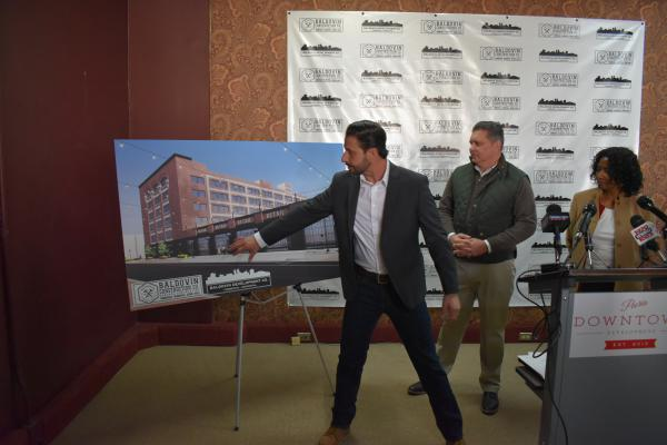 Developer Casey Baldovin shows his vision for the buildings he purchased on SW Adams. Councilman Sid Ruckriegel and Councilwoman Denise Moore look on.