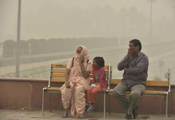 People cover their faces with masks to avoid thick smog in New Delhi on Nov. 5. People living there have complained about respiratory problems.