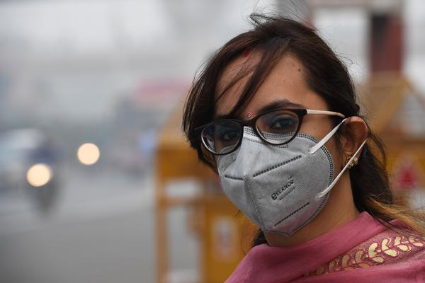 A woman wearing a protective face mask waits for a bus in New Delhi. The city experienced record levels of toxic smog this week.