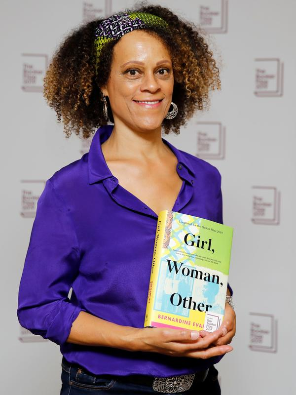 British author Bernardine Evaristo poses with her book <em>Girl, Woman, Other</em>. She would later win the 2019 Booker Prize for Fiction, an honor she shared with Margaret Atwood.